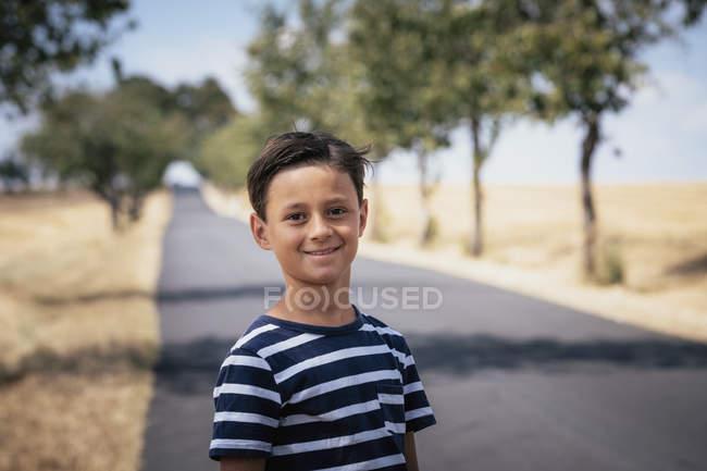 Портрет уверенный мальчик на солнечной сельской дороге — стоковое фото
