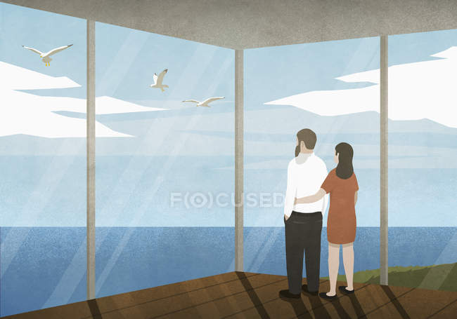 Пара, насолоджуючись видом на океан з будинку пляж — стокове фото
