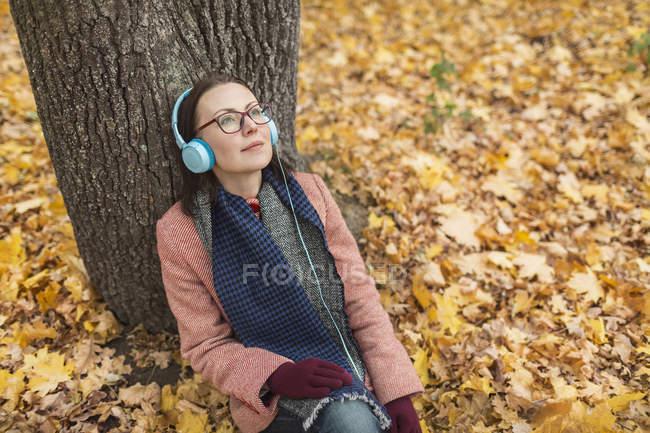 Спокойная женщина слушает музыку в наушниках под деревом в осеннем парке — стоковое фото