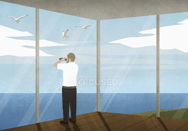Человек с биноклем наслаждается видом на океан из пляжного домика — стоковое фото