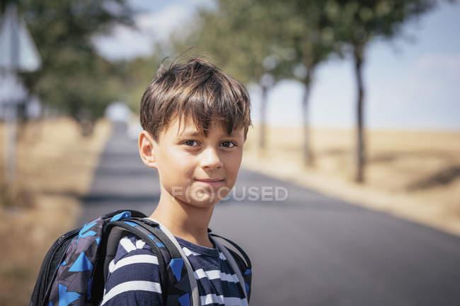 Portrait écolier confiant avec sac à dos sur route ensoleillée — Photo de stock