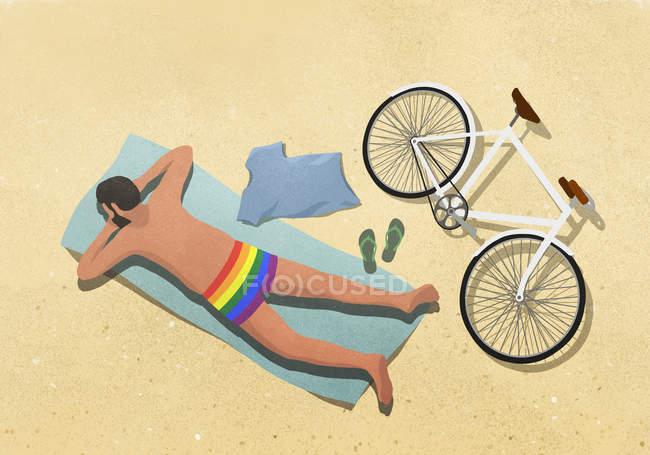 Homem de sunga arco-íris, sol na toalha de praia — Fotografia de Stock