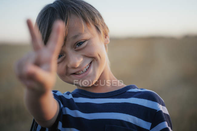 Portrait smiling, carefree boy gesturing peace sign — стокове фото