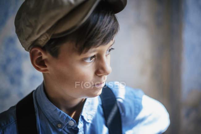 Thoughtful boy in cap looking away — Stock Photo