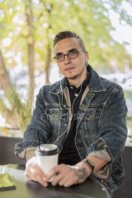 Mann hört Musik mit Ohrhörern, trinkt Kaffee im Café — Stockfoto