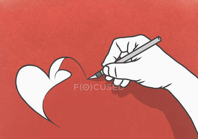 Hand cutting heart-shape out of red paper with scalpel — Stock Photo