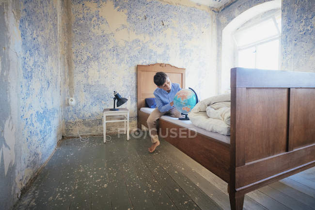 Boy looking at globe on rustic farmhouse bed — Stock Photo