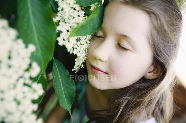 Ragazza serena appoggiata al fiore — Foto stock