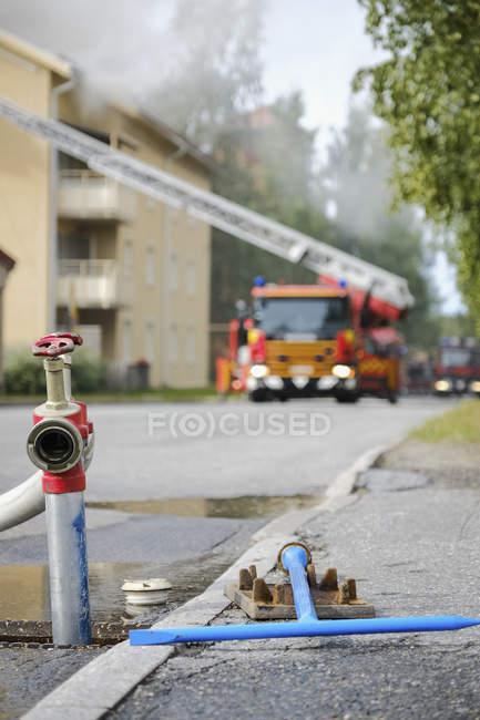 Caminhões de bombeiros que tendem a apartamento fogo com fogo aberto hidrante em primeiro plano — Fotografia de Stock
