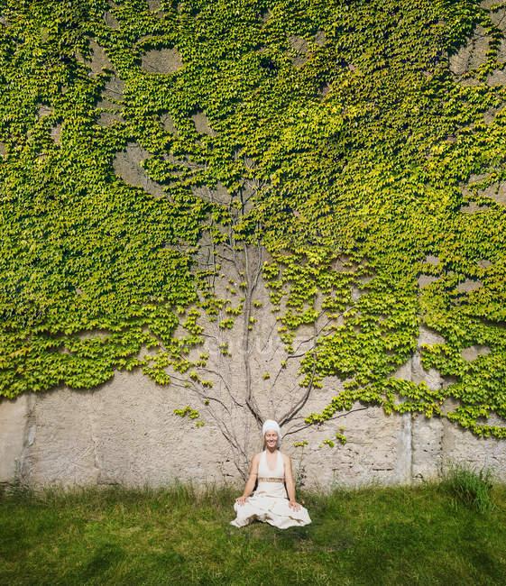 Porträt einer meditierenden Frau an einer mit Efeu bewachsenen Mauer — Stockfoto