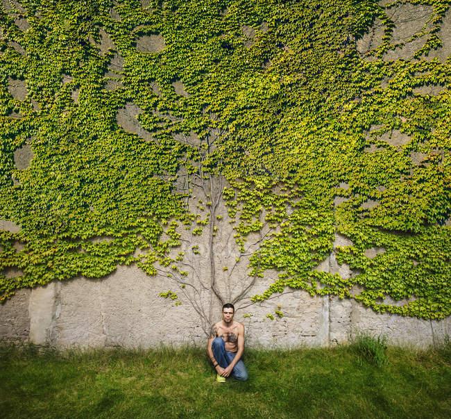 Porträt eines Mannes mit tätowierter Brust, der an einer mit Efeu bewachsenen Wand sitzt — Stockfoto