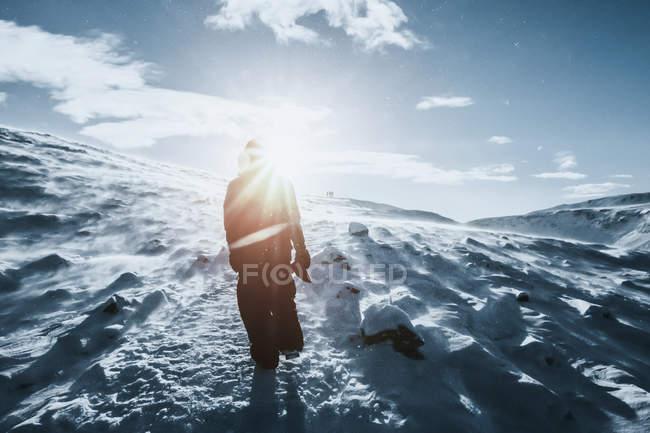 Man walking along sunny snow covered landscape, Reykjadalur, Iceland — Stock Photo