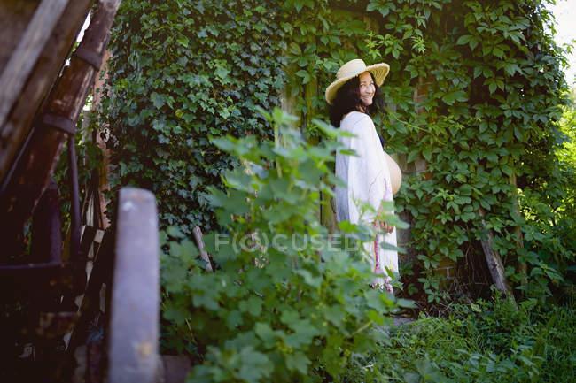 Retrato mujer embarazada feliz de pie en la puerta cubierta de hiedra - foto de stock