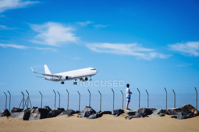 Boy on beach watching airplane flying low in blue sky near Lanzarote Airport, Spain — стоковое фото