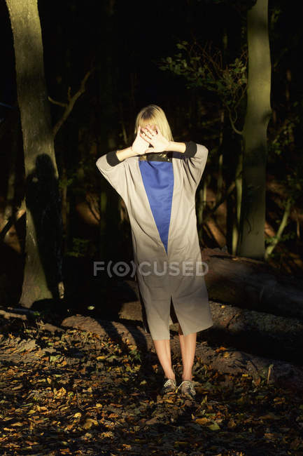 Портрет женщины, покрывающей лицо в лесу — стоковое фото