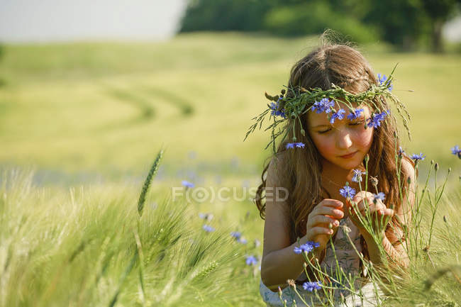 Curious girl with wildflowers in hair in sunny, rural wheat field — Stock Photo