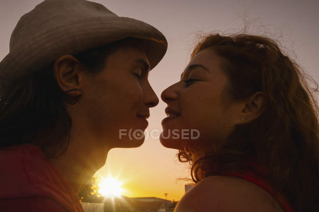Affectionate couple kissing with sunset in background — Stock Photo