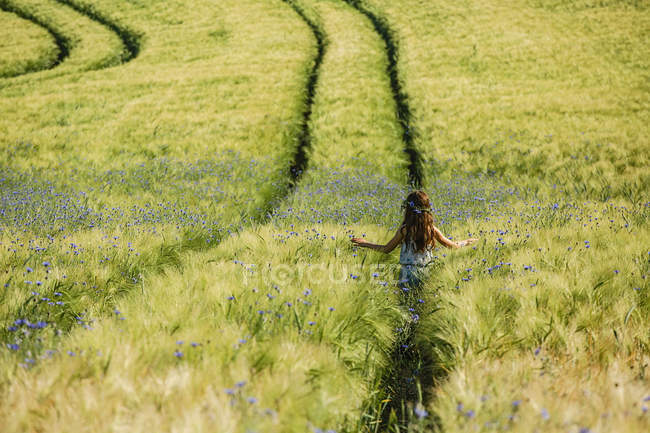 Carefree girl walking in sunny, idyllic rural field with wildflowers — стоковое фото