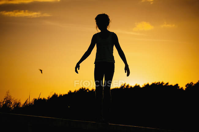 Silhouette of woman standing against sunset sky — Stock Photo