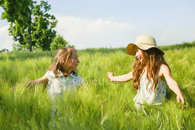 Happy, carefree sisters in sunny, idyllic rural green wheat field — Stock Photo
