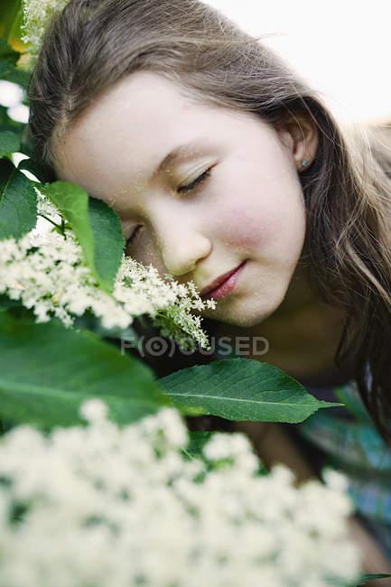 Спокойная девушка опирается на цветущий куст — стоковое фото