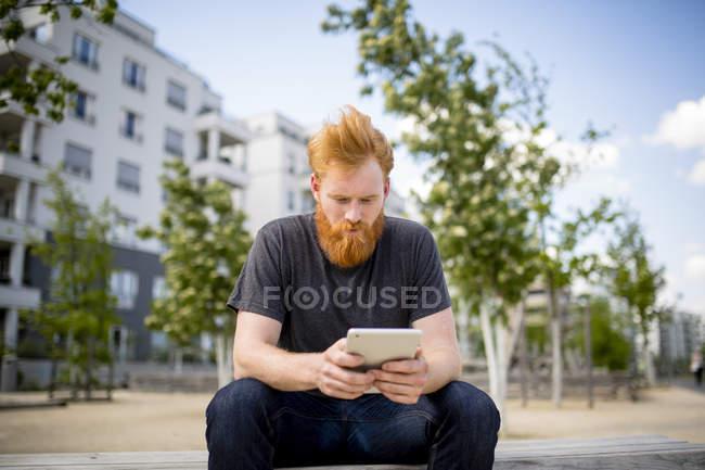 Человек с бородой с помощью цифрового планшета на городской скамейке — стоковое фото
