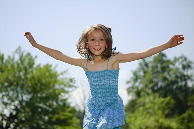 Ritratto giocoso ragazza con le braccia tese saltando per la gioia nel cortile soleggiato — Foto stock