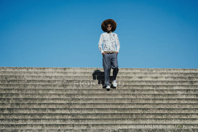 Portrait confident, cool young man with afro on sunny steps — Stock Photo