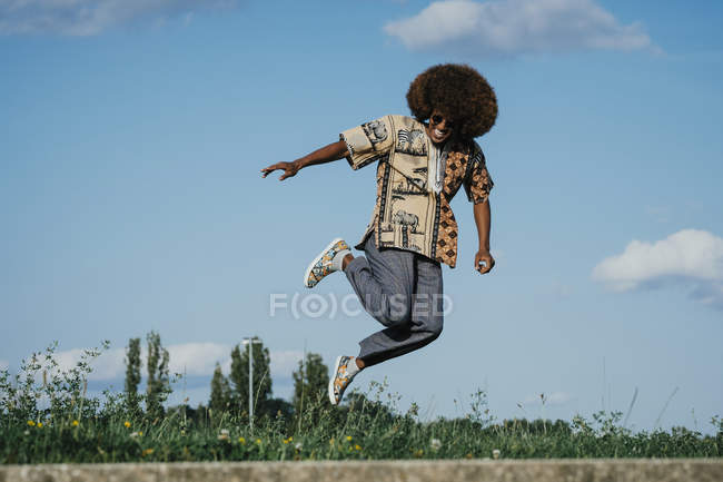 Carefree young man with afro jumping for joy — Stock Photo