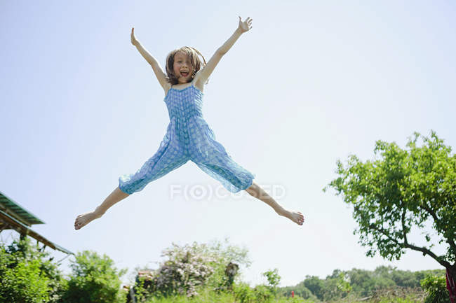 Portrait playful, carefree girl jumping for joy in back yard — Stock Photo