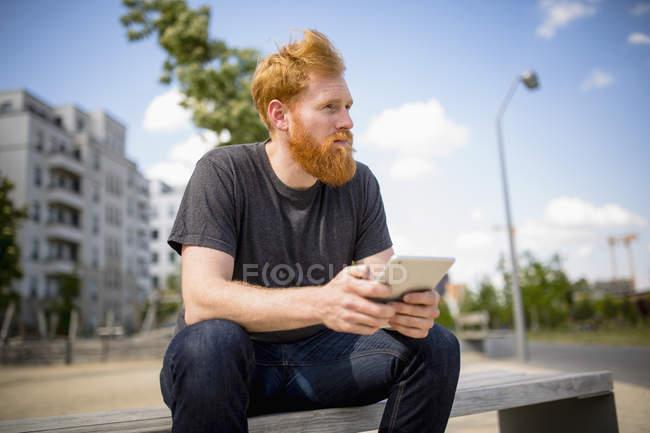 Хипстер человек с бородой с помощью цифрового планшета на городской скамейке — стоковое фото