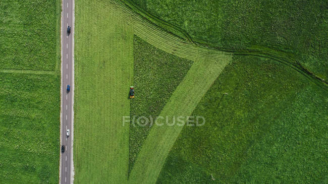 Drone point of view tractor harvesting lush green farmland crop, South Tyrol, Italy — Stock Photo