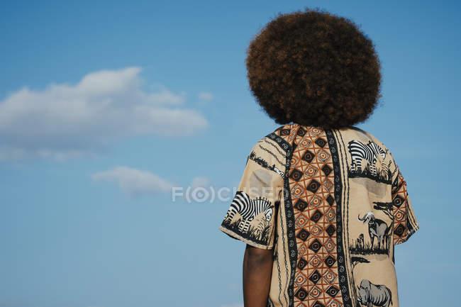 Молодий чоловік з африканцем, який дивиться на хмари на синьому небі. — стокове фото