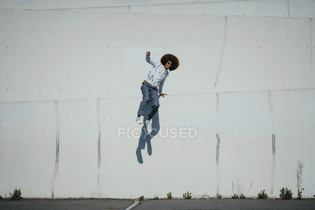 Portrait carefree young man with afro jumping at sunny wall — Stock Photo