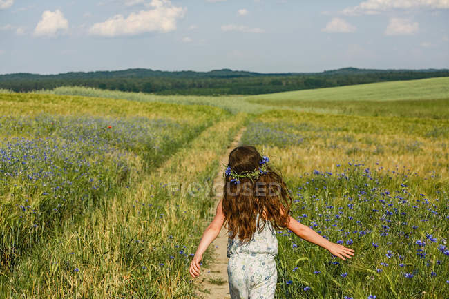 Девушка бегает по солнечному, сельскому идиллическому зеленому полю с полевыми цветами — стоковое фото