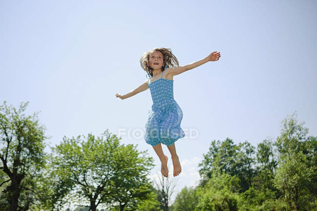 Carefree girl in dress jumping for joy in sunny backyard — Stock Photo