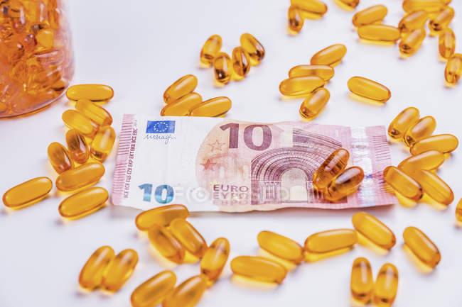 Медицинские капсулы и банкнота в 10 евро — стоковое фото