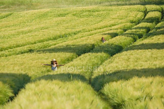 Беззаботные девушки бегают на солнечном, идиллическом зеленом сельском пшеничном поле — стоковое фото
