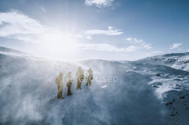 Pessoas caminhando ao longo da paisagem ensolarada, ventosa, coberta de neve, Reykjadalur, Islândia — Fotografia de Stock