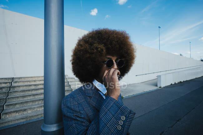 Giovane ben vestito con sigaretta afro fumare sul marciapiede urbano — Foto stock