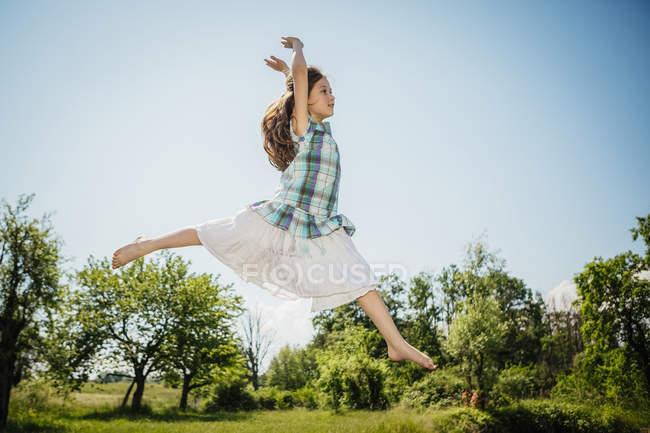 Ragazza spensierata in abito saltando per la gioia nel cortile soleggiato — Foto stock