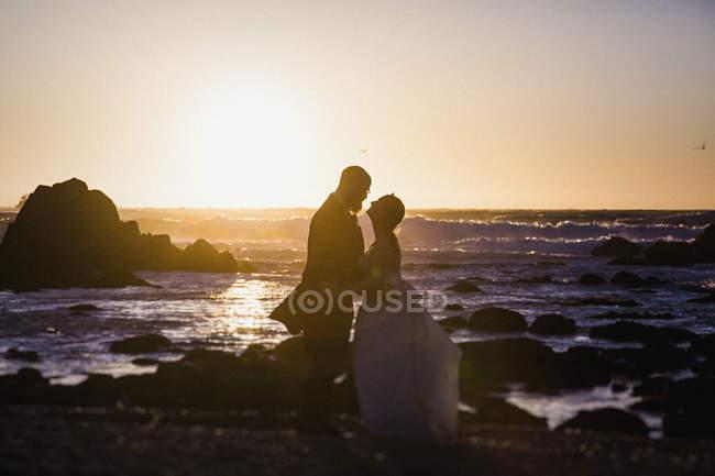 Noiva silhueta e noivo na tranquila praia do oceano por do sol, Monterey, Lucas Point, Califórnia, EUA — Fotografia de Stock