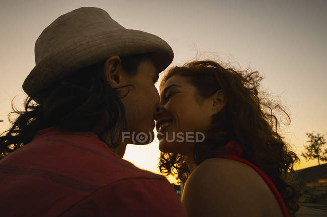 Affectionate couple kissing at sunset — Stock Photo