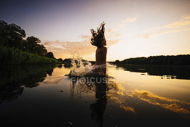 Carefree girl jumping into lake at sunset, Barnin, Mecklenburg-Vorpommern, Germany — Stock Photo