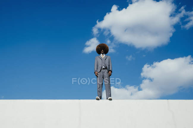 Portrait confident, cool, well-dressed young man with afro standing on wall against sky — Stock Photo