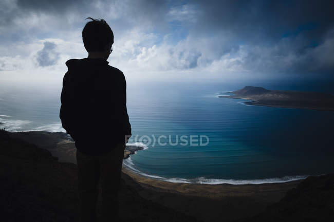 Boy looking at scenic ocean bay view with storm clouds overhead, Lanzarote, Canary Islands, Spain — Stock Photo