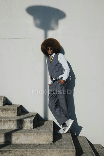 Portrait confident, cool, well-dressed young man with afro on urban steps — Stock Photo