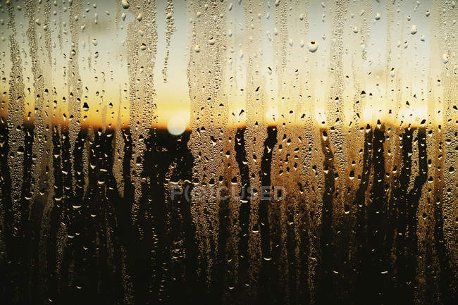 Raindrops and condensation on window with scenic sunset view — Stock Photo