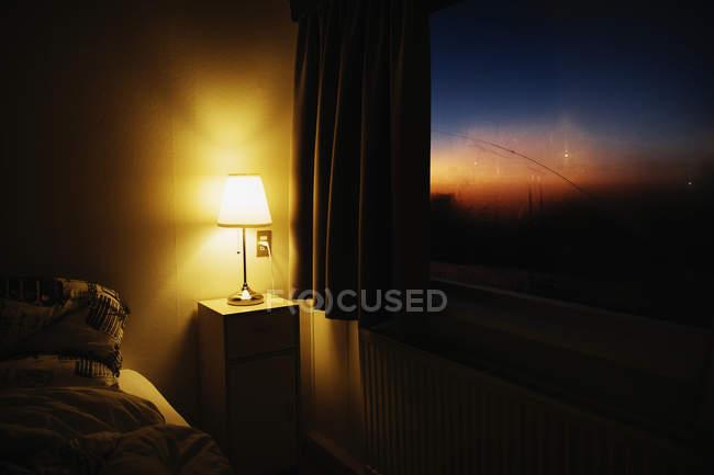 Canto iluminando do quarto da lâmpada de cabeceira ao lado da janela com vista do céu do Crepúsculo — Fotografia de Stock