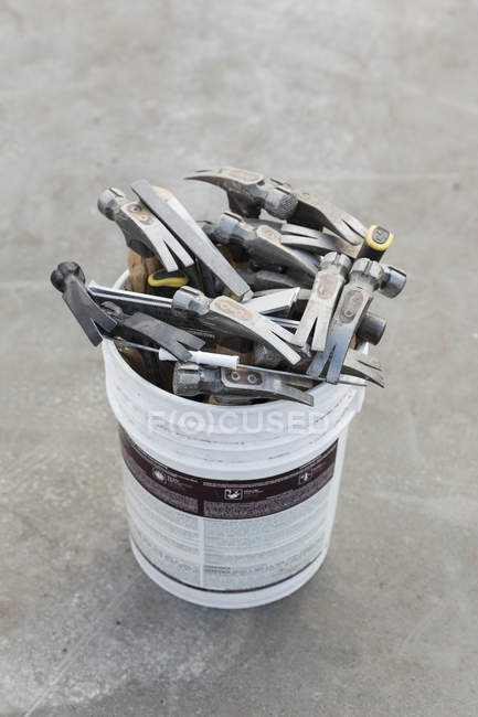 Hammers in bucket over grey surface — Photo de stock